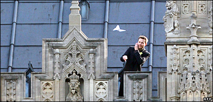 A protestor throws a paper aeroplane from the roof of the Houses of Parliament