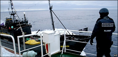 A Japanese coastguard official stands guard on a whaling ship as activists approach in their own boat