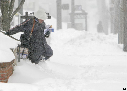 A postman battling through the snow to make his deliveries