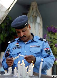 Iraqi policeman lights candle outside Chaldean Catholic church in central Baghdad