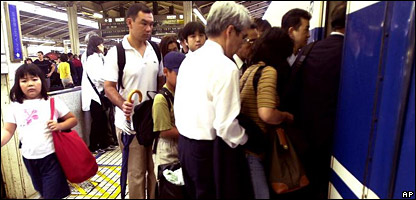 Japanese commuters piling onto a tube train