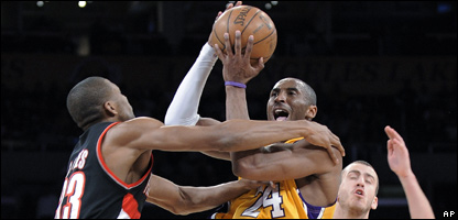 Los Angeles Lakers guard Kobe Bryant, centre, shoots over Portland Trail Blazers forward James Jones