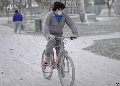 Man on bike covered in ash