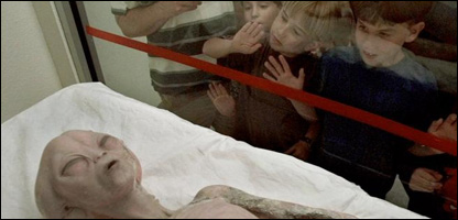 Children eye a model of an alien on display inside the International UFO Museum in America