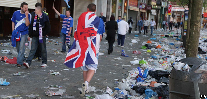 A Rangers fan walks past Zenit fans in Manchester
