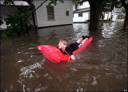 Shane 11, paddles about the flooded streets