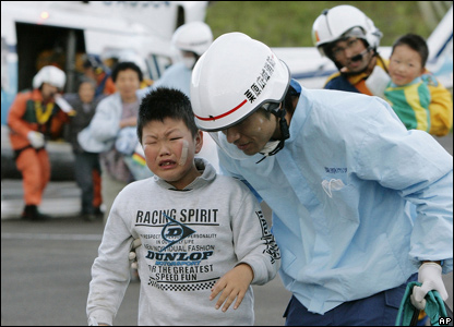A rescuer escorts a boy from a helicopter (AP Photo/Kyodo News)