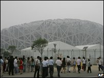 Visitors looking at the National Stadium, known as the Bird's Nest