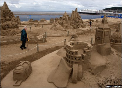People stop to look at the sand sculptures
