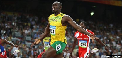 Usain Bolt of Jamaica celebrates as he crosses the line