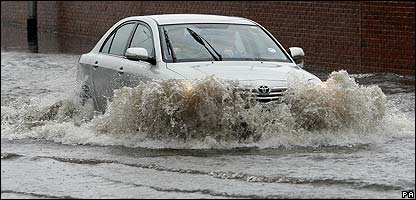 Car in Northern Ireland drives along a flooded road