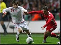 Georgia's Levan Kenla (left) and Wales' Jason Koumas battle for the ball