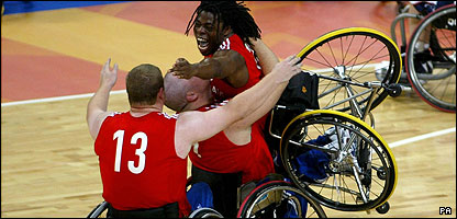 Ade Adepitan celebrates with his Great Britain wheelchair basketball team-mates at the 2004 Paralympics