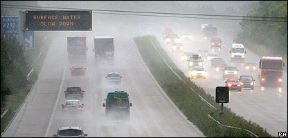 Cars on a motorway struggle with rain