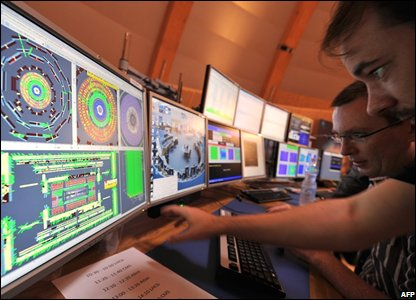 scientists look at computer screens showing traces on the Atlas experiment of the first protons
