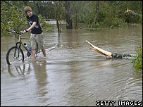 Boy drives a bicycle along flooded road