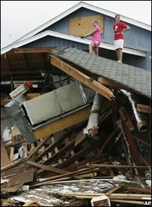 People standing on the roof of a damaged house (AP Photo/Houston Chronicle, Julio Cortez)