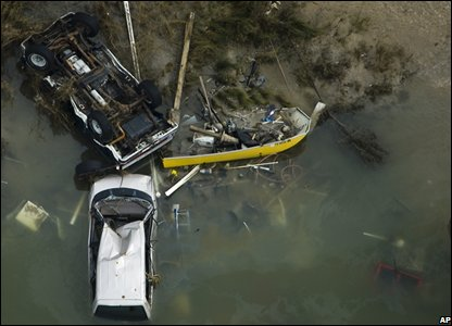 Overturned automobiles and boats in Gilchrest  (AP Photo/Pool, Smiley N. Pool)