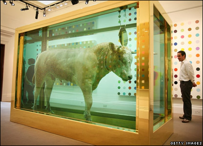 "A man looking at Damien Hirst's artwork ""The Golden Calf"""