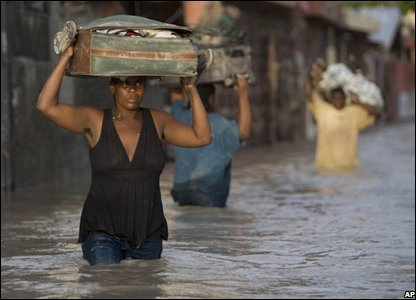 A resident carries a suitcase on her head as she wades through a flooded street in Gonaives, Haiti (AP Photo/Ariana Cubillos)