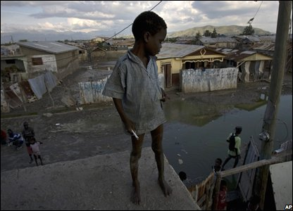 A boy stands on the roof of a shelter for flood victims