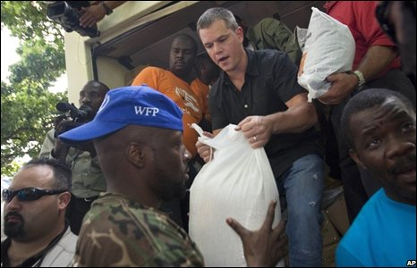 Actor Matt Damon, top center gives a sack of rice to  Wyclef Jean(AP Photo/Ariana Cubillos)
