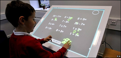 A school boy tries out one of the interactive desks