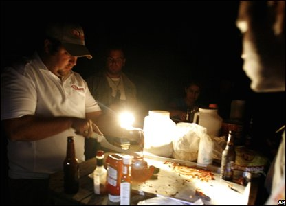 Man cuts up food by flashlight (AP Photo/LM Otero)