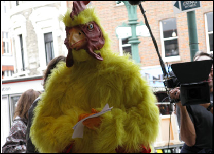 Person in a chicken suit and a cameraman