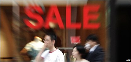 Shoppers pass a sale sign (Photo: YOSHIKAZU TSUNO/AFP/Getty Images)