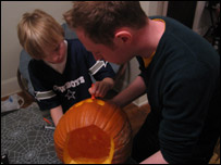 Adam helps Colin to carve a pumpkin