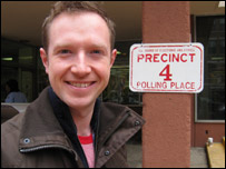 Adam next to a polling sign