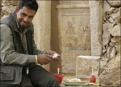 An archaeology worker cleans hieroglyphic details on a white limestone casing at the site of a newly-discovered pyramid near Cairo in Egypt