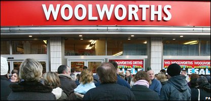 Shoppers wait to go into Woolworths as the sale begins