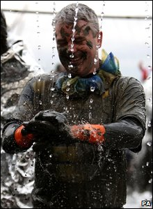 Competitor Dominic Finn, from Maldon, smiles as he showers off mud  (Photo by Chris Radburn/PA Wire)