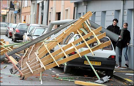 Part of a roof structure lies across a car following a storm in Toulouse, France