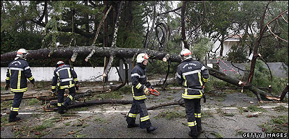 Public roads workers clear away trees felled by the storm in France