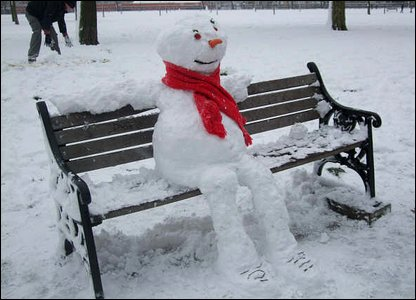 Cool snowman on a park bench