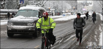 A driver, cyclist and runner making their way through the snow