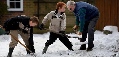 Children helping to clear snow from a school's driveway