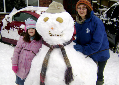 Esme and her mum with the snowman they made