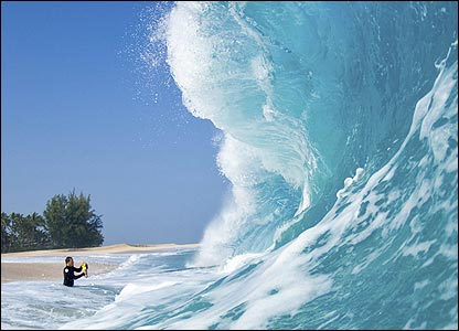 Here he is standing in front of a massive wave which is about to break on the shoreline.
