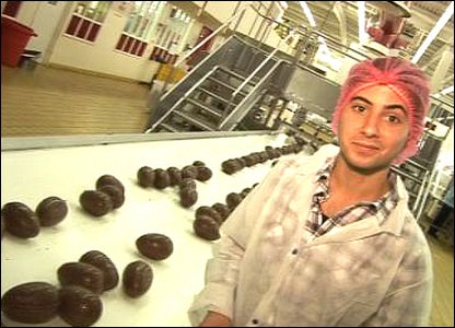 Ricky next to a conveyor belt of Easter eggs.