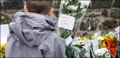A young boy leaves flowers at the scene (Photo by Paul Faith/PA Wire)