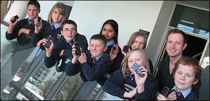 Newsround's Adam and children with mobile phones
