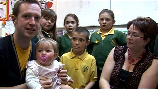 Adam with baby Rebecca and pupils and at the school