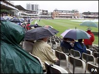 Cricket fans shelter from the rain at Lords (PA Photo: Tom Hevezi)