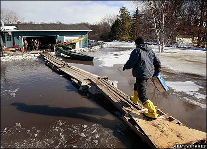 A man uses a bridge to his home in Dakota
