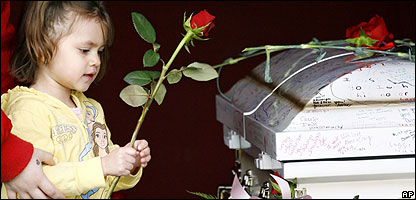 A child puts a flower on a coffin in America