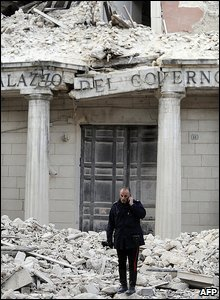 A policeman talks on a phone in front of a damaged building in the centre of L'Aqulia